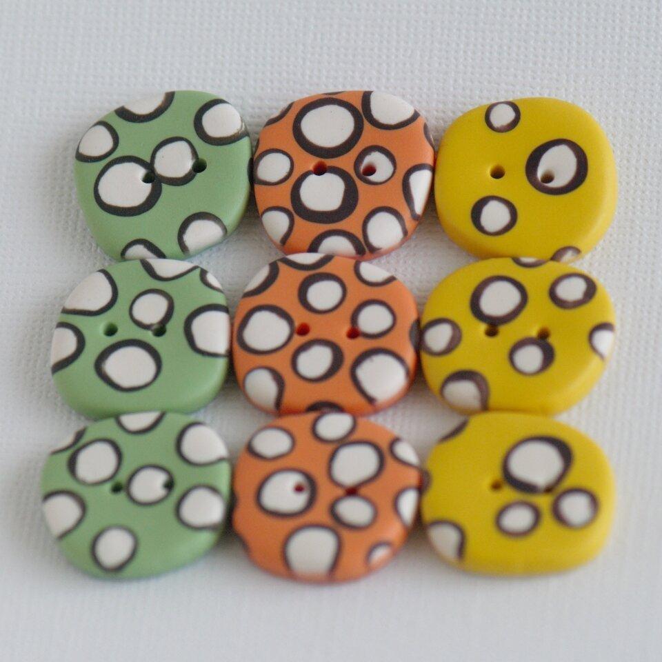 21 mm – 9 vnt. netaisyklingos apvalaino keturkampio formos oranžinės, žalios ir geltonos sagos su žaismingais rutuliukais