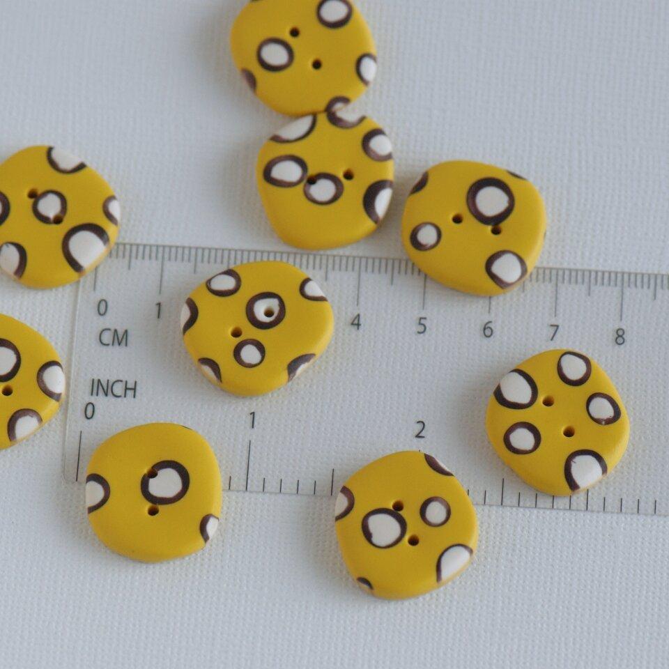 21 mm – 9 vnt. netaisyklingos apvalaino keturkampio formos geltonos taškuotos sagos